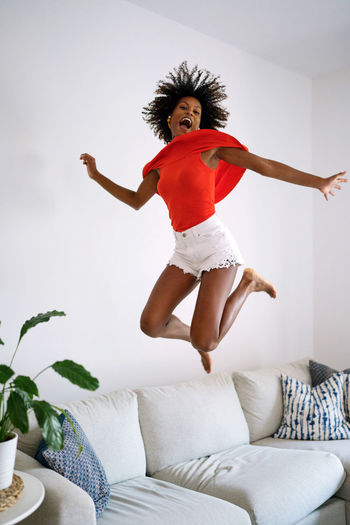 Full length portrait of happy young woman jumping on bed at home