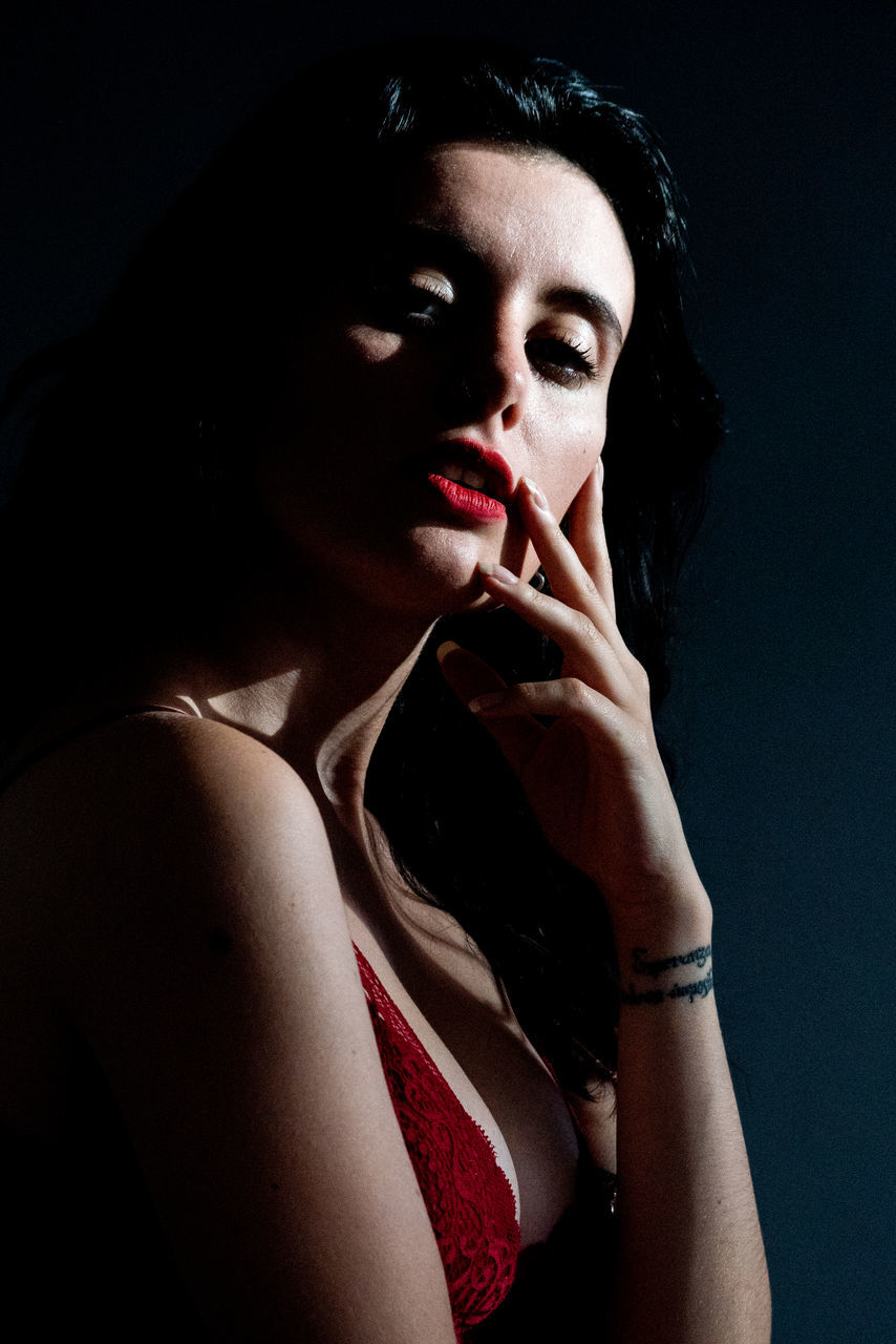 young adult, one person, indoors, portrait, young women, make-up, lipstick, front view, lifestyles, red lipstick, looking, women, red, hand on chin, beautiful woman, studio shot, looking at camera, real people, black background, contemplation, dark, hairstyle, finger on lips, human lips