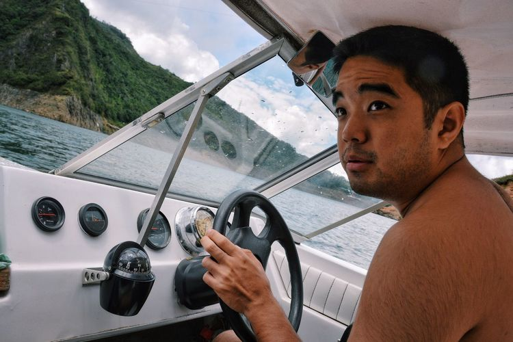 Young man driving boat