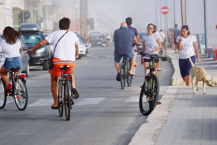 Bicycle Transportation Riding Mode Of Transport Cycling Men Full Length Women Day Group Of People Land Vehicle Outdoors City Built Structure Real People Sitting Building Exterior Architecture Adult Young Adult Travel Destinations Sicilia Italy Summer Foggy