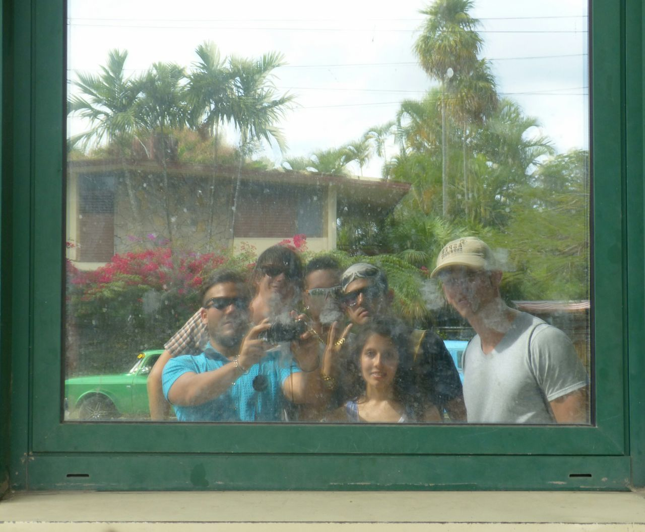 tree, day, leisure activity, window, togetherness, real people, lifestyles, enjoyment, men, motion, standing, outdoors, palm tree, happiness, group of people, boys, large group of people, women, nature, friendship, young women, young adult, people, adult, sky