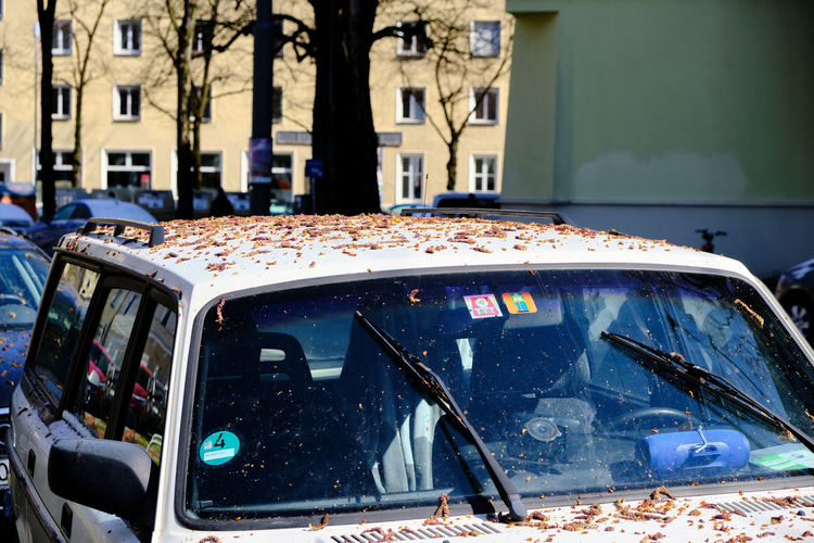 Close-up of abandoned car against buildings in city
