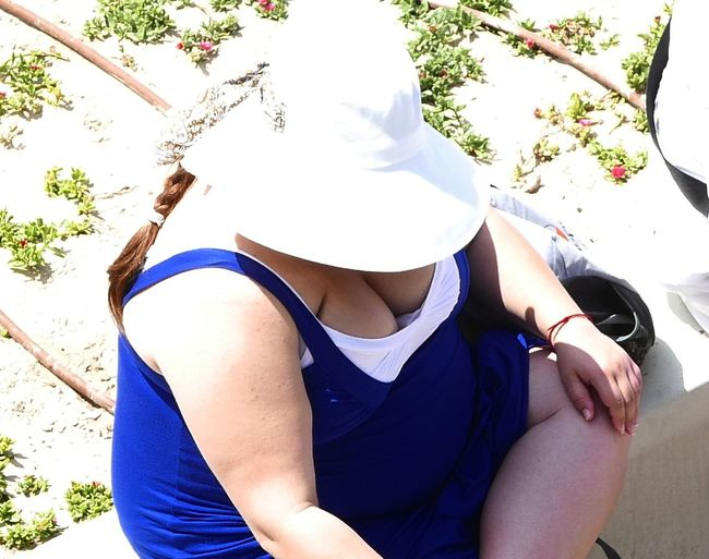 overweight woman with white hat and summer blue dress view from above Obesity Overweight Woman