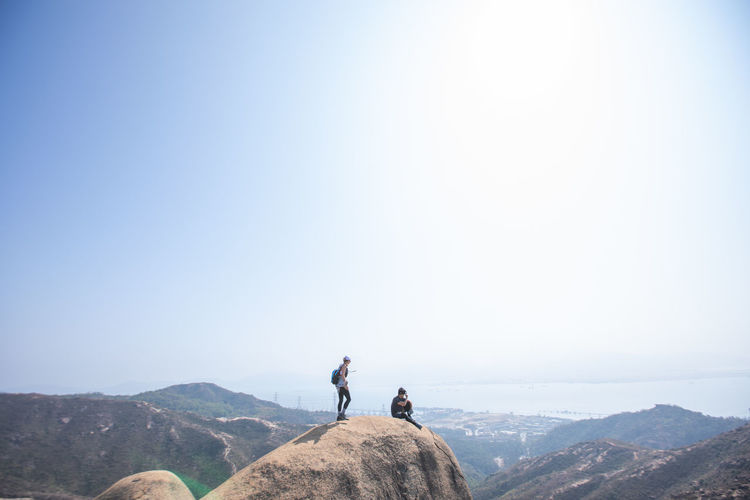 People standing on mountain against clear sky