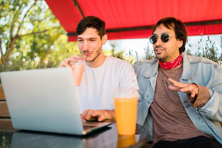 Smiling men using laptop sitting outdoors