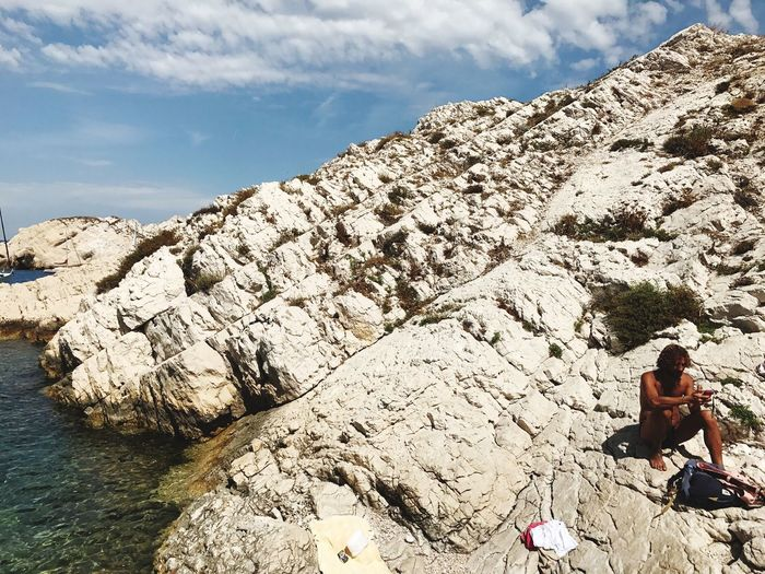 Shirtless Man Sitting On Rock Formation By Sea At Frioul Archipelago