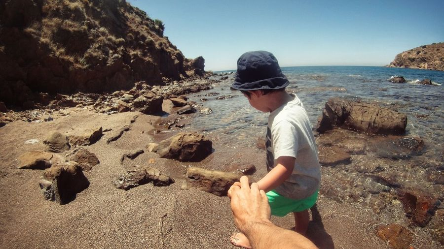 Cropped Image Of Person Holding Boy Hand At Shore