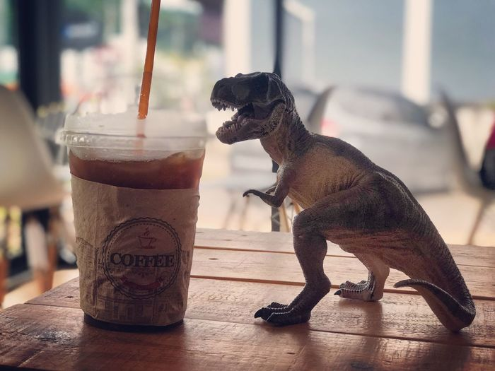 Ice coffee with dinosaurs on table in coffee shop EyeEm Selects Refreshment Drink Table Food And Drink Focus On Foreground Glass Drinking Glass Household Equipment Drinking Straw No People Straw Animal Representation Day Still Life Representation Animal Freshness Close-up Animal Themes Cold Temperature