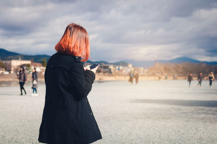 Woman using mobile phone against cloudy sky