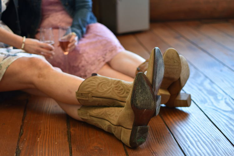 Low section of friends holding drinks on hardwood floor