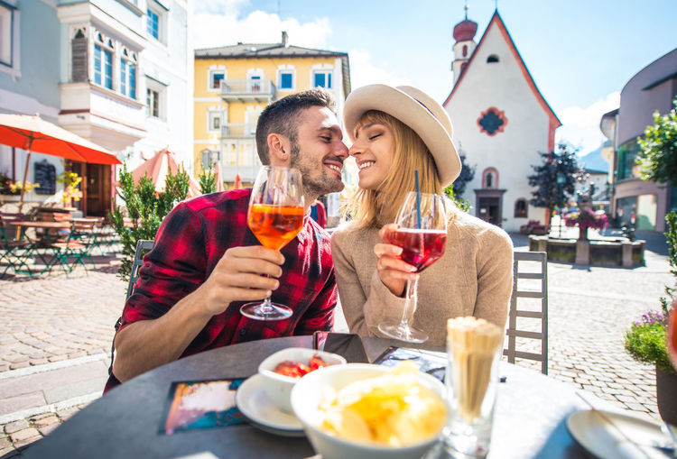 Smiling couple holding wineglass embracing while sitting at cafe outdoors