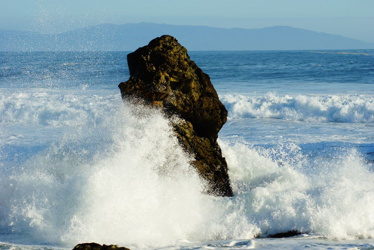 Waves Crashing On Rock Formation In Sea