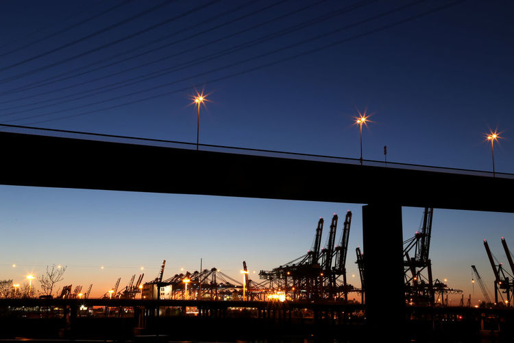 Hamburg Harbour with Koehlbrand bridge with dockside cranes in the background at dusk with orange lights and crisp blue sky Architecture Bridge - Man Made Structure City Clear Sky Dockside Crane Dockside Cranes Finkenwerder Hafen Hamburg Hamburg Harbor Hamburg Harbour Harbour View Illuminated Köhlbrand Köhlbrandbrücke Moon Nature Nautical Vessel Night No People Outdoors Silhouette Sky Sunset Waltershofer Hafen