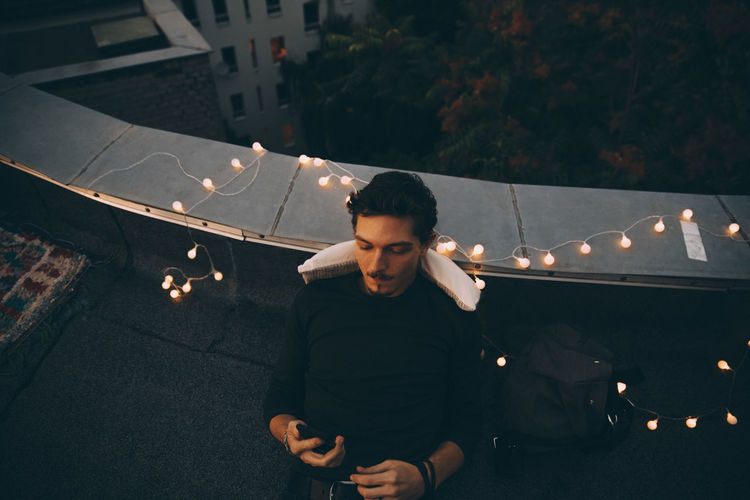 High angle view of young man looking away at night