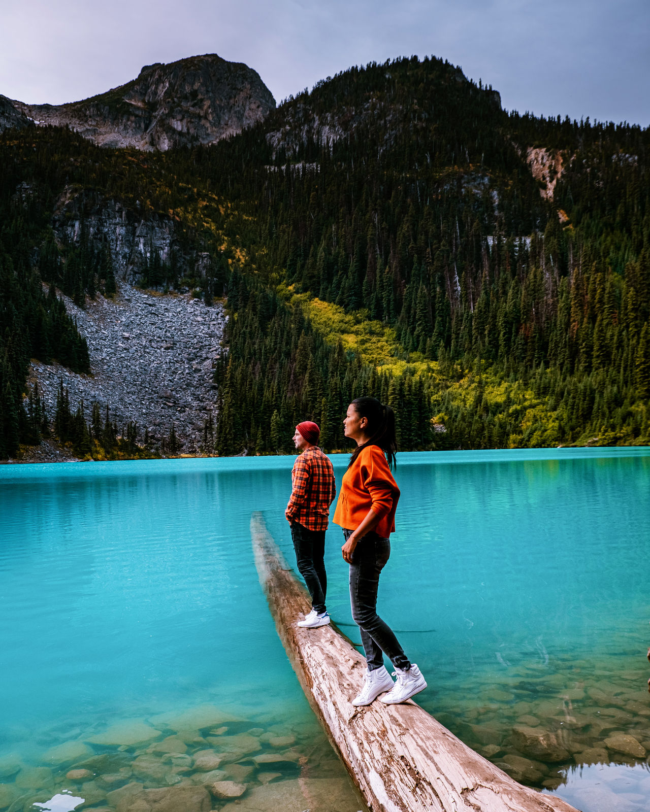 Couple standing on wood by lake against mountain