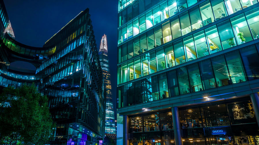 Low Angle View Of Illuminated Modern Buildings And Shard London Bridge