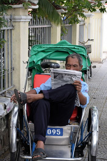 Rickshaw driver having a break in Hoi An, Vietnam Adult Adults Only Day Full Length Land Vehicle Lunch Break Mode Of Transport Newspaper Reading One Man Only One Person Only Men Outdoors People Rickshaw Rickshaw Driver Sitting Transportation Vietnam