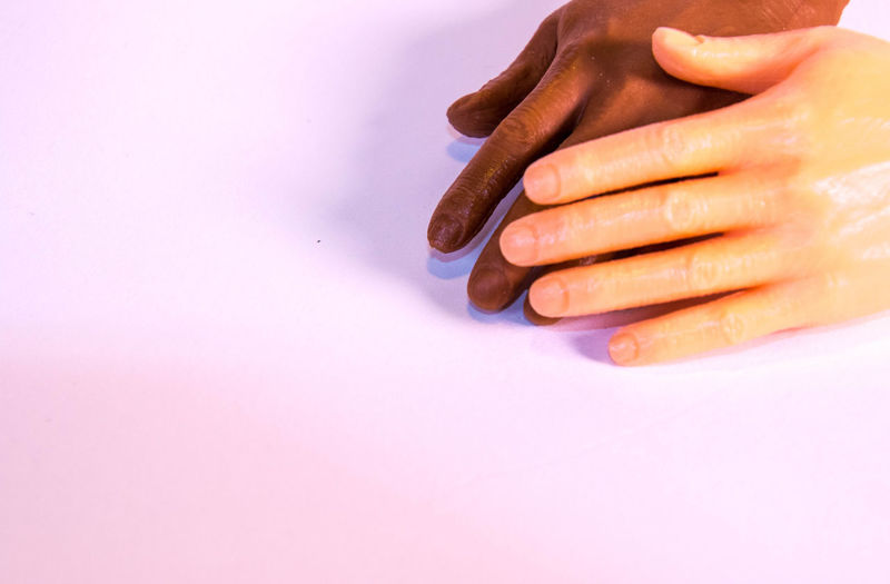 Close-up of woman hand over colored background