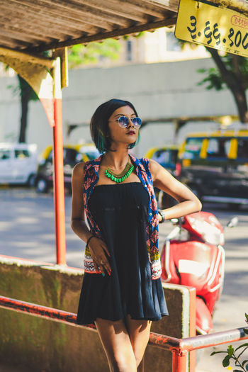 Woman in sunglasses standing at bus stop