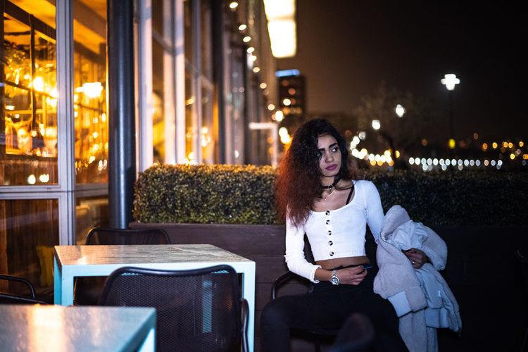 Woman sitting on chair at sidewalk cafe