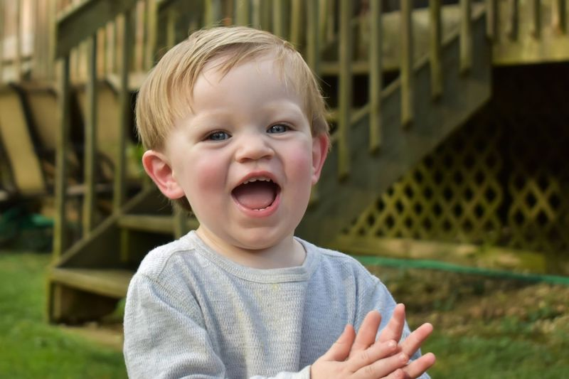 Portrait Of Laughing Baby Boy Standing At Yard