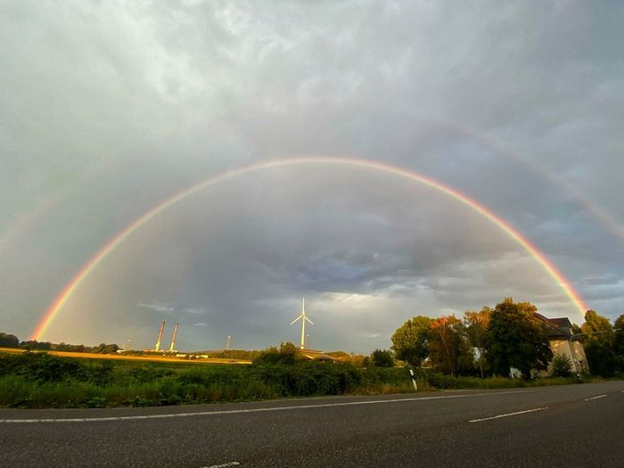 Rainbow over road against sky