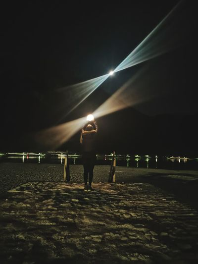Rear view of man standing on footpath at night