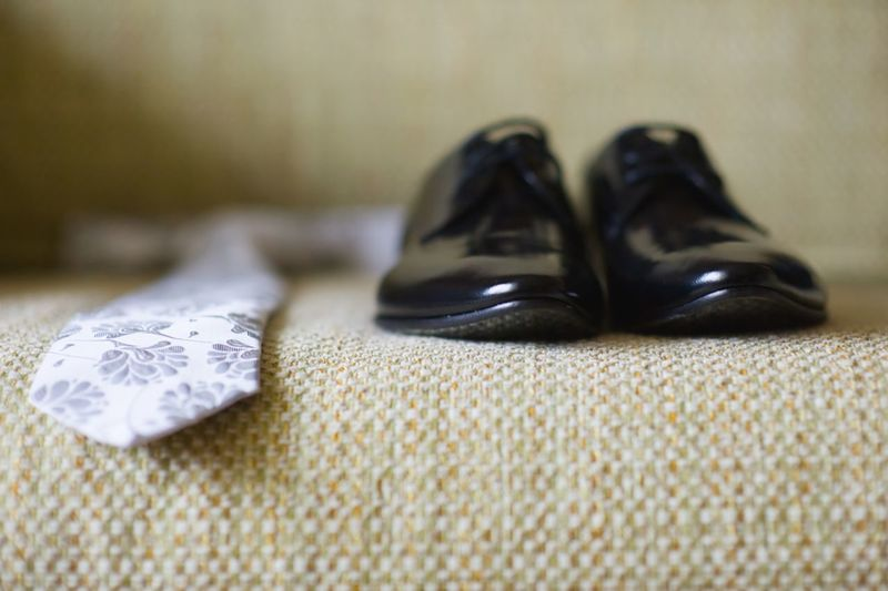 Necktie and shoes on sofa at home