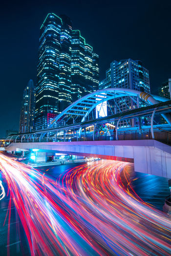 Light trails on illuminated buildings in city at night