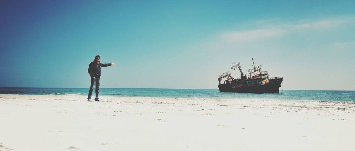 Mid distance view of man pointing towards shipwreck in sea against sky