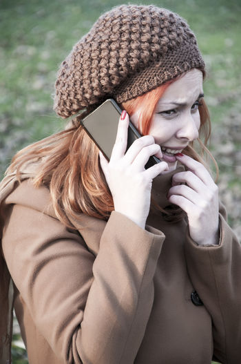 Beautiful woman wearing warm clothing while using smart phone in park