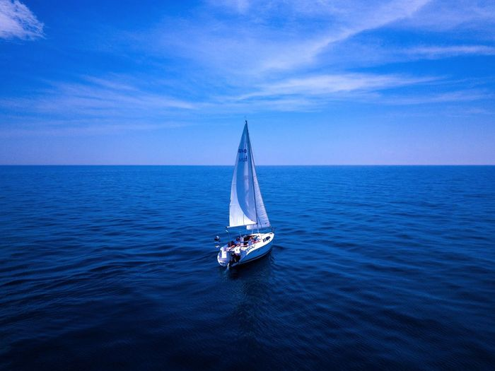 Sailboat Sailing In Sea Against Sky