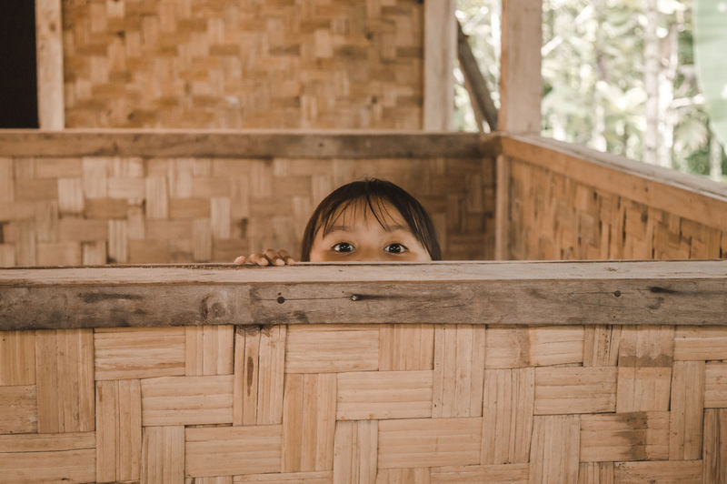 Portrait of girl hiding behind retaining wall