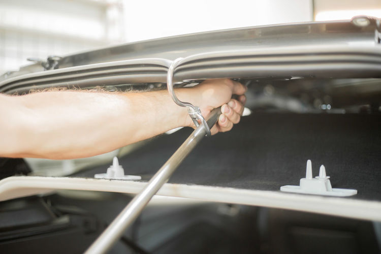 Cropped Hand Of Mechanic Repairing Car