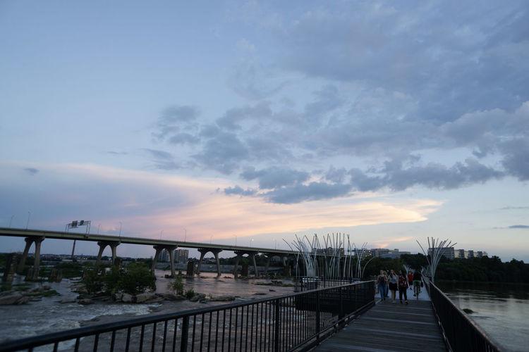 People on footbridge against sky during sunset