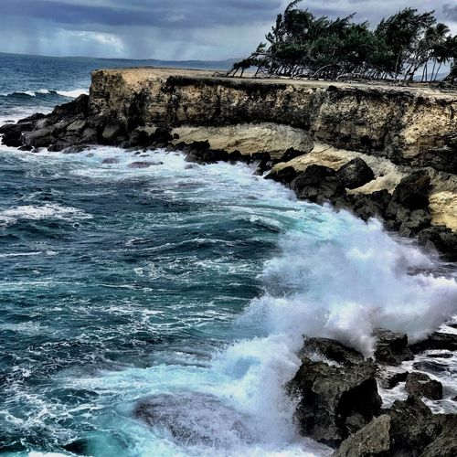 Windswept coast Tropical Windswept Water Power In Nature Motion Rock - Object Sea Wave Nature Beauty In Nature Rock Formation Surf Rock Rough Breaking Outdoors No People Day Crash Sky Scenics Cliff