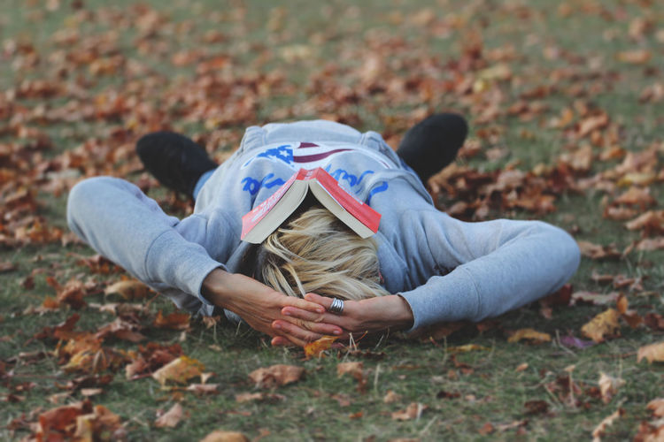 Mature woman lying down on field during autumn