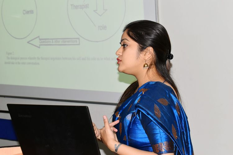 Side View Of Young Woman Wearing Blue Sari Having Business Meeting