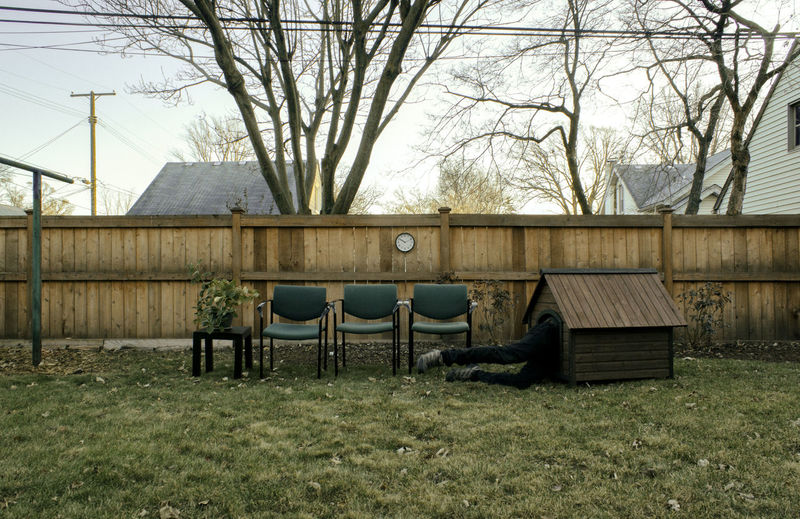 Chairs and bare trees on field by house against sky
