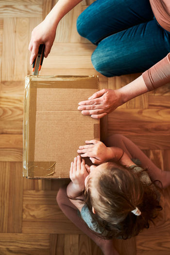 Woman unpacking a cardboard box parcel in room at home. little girl waiting for opening a box