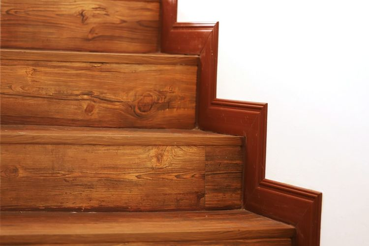 Wooden staircase against wall at home