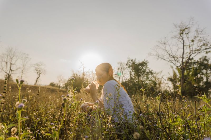 Beautiful sun and grass. Outdoors Relaxing Nature Blur Drink Flower Grass Beautiful Plant One Person Flower Nature Sky Flowering Plant Growth Field Lifestyles Tree Sunlight Day Real People Casual Clothing Leisure Activity Beauty In Nature Land Tranquility