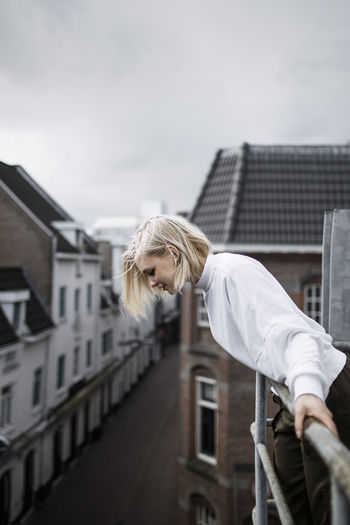 Woman standing by building against sky in city