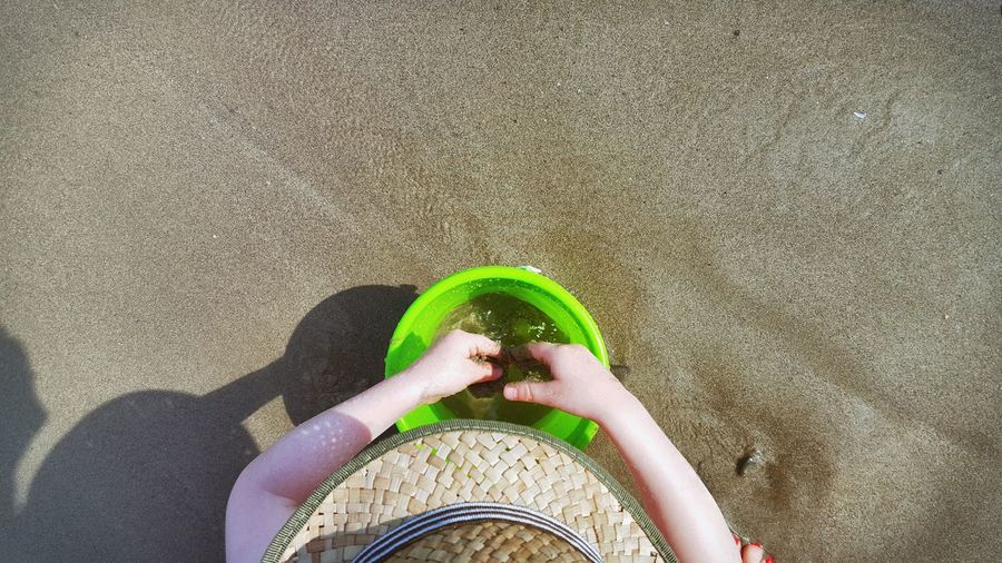 Cropped image of boy with bucket at beach