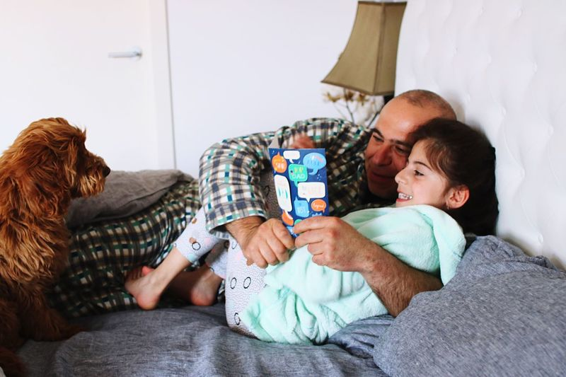 Man with daughter by dog reading book on bed at home