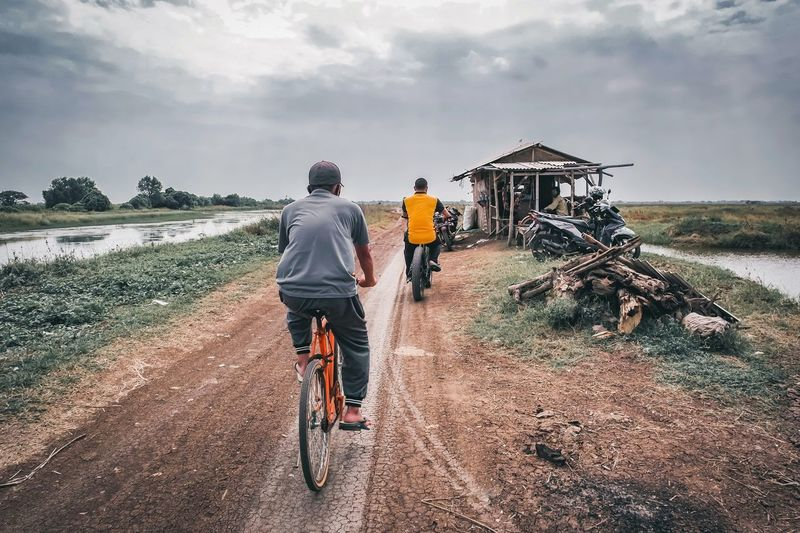 Rear view of man riding bicycle on road against sky