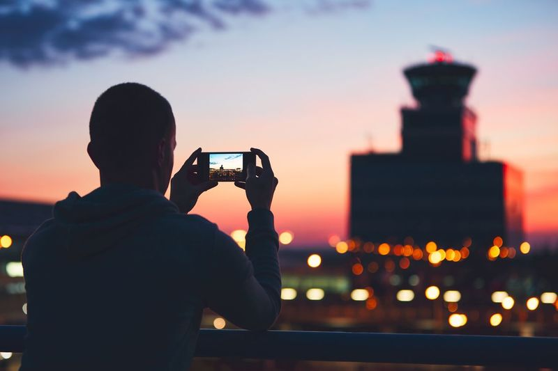 Rear view of man photographing at sunset