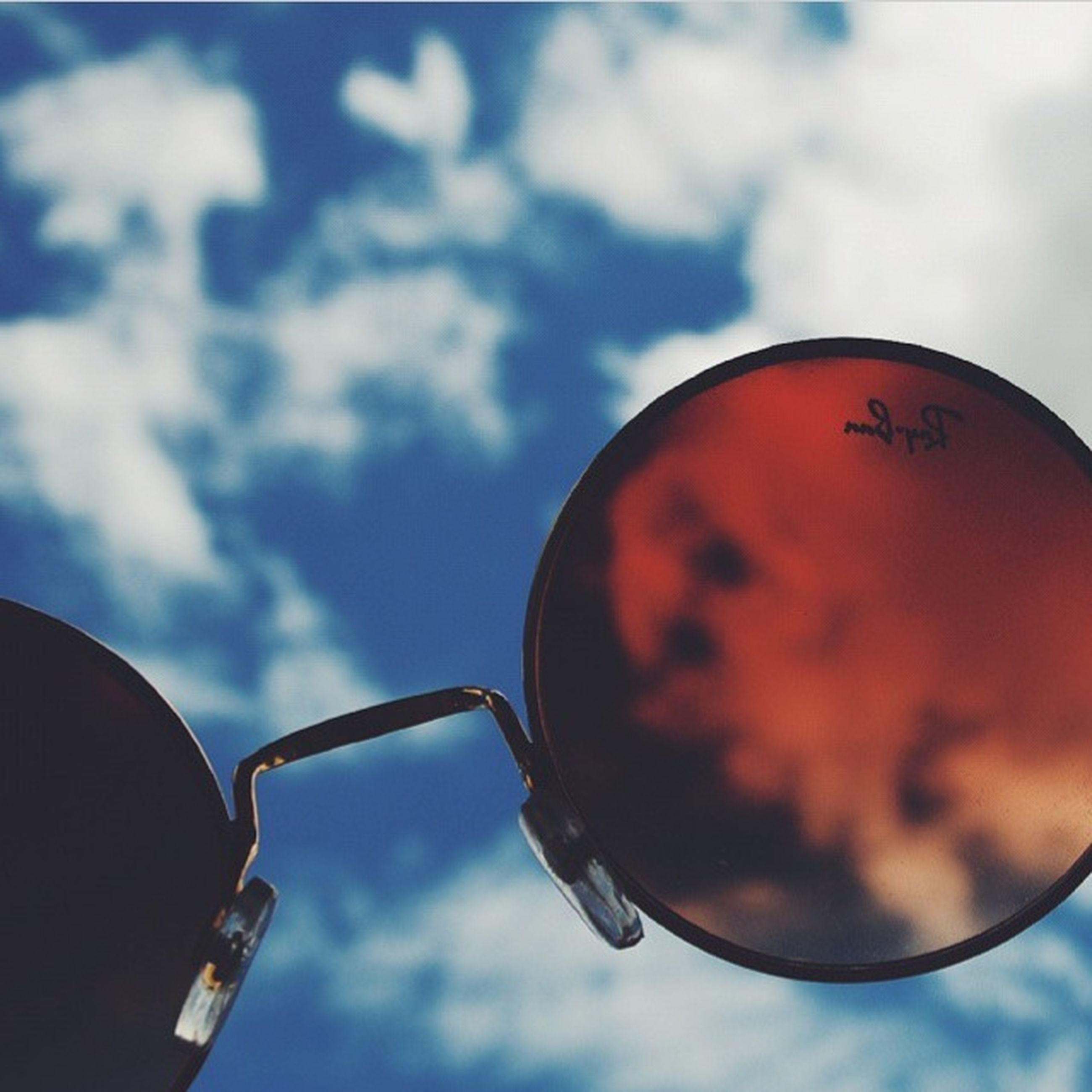 low angle view, sky, close-up, communication, text, focus on foreground, cloud - sky, metal, circle, lighting equipment, no people, outdoors, hanging, day, safety, red, cloud, western script, sphere, lantern