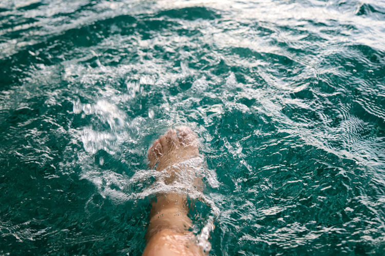 Low section of person feet in swimming pool
