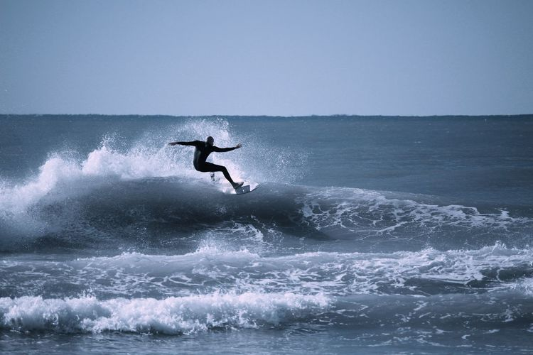View of a silhouette man surfing in the sea
